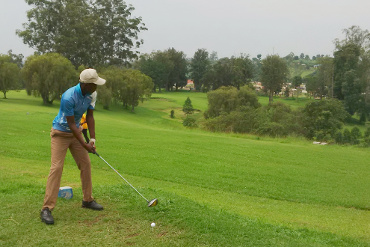 taking a swing at the 9-hole parkland golf course in Fort Portal